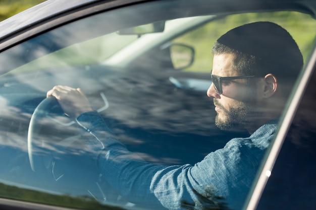 Samiec z okularami przeciwsłonecznymi jedzie samochód