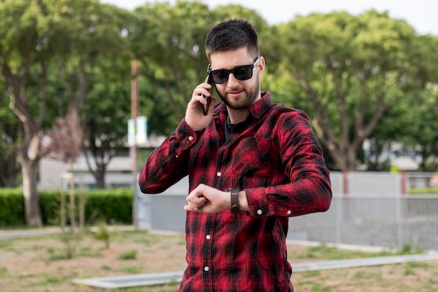 Samiec z okularami przeciwsłonecznymi trzyma smartphone blisko ucho i patrzeje zegarki
