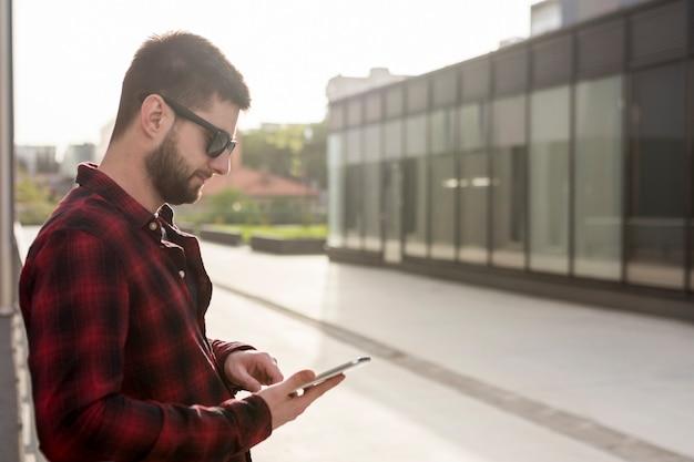 Samiec z okularami przeciwsłonecznymi używać smartphone
