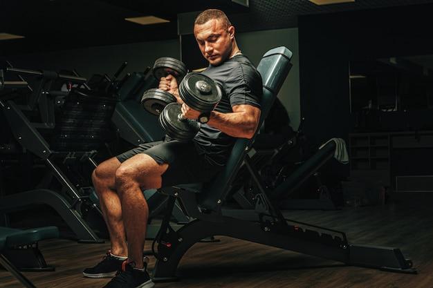 Samiec z sporta ciała podnośnymi dumbbells przy gym