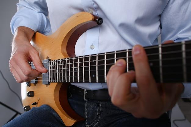 Samiec zbroi trzymać klasycznego kształta drewnianego gitary elektrycznej zbliżenie i bawić się.