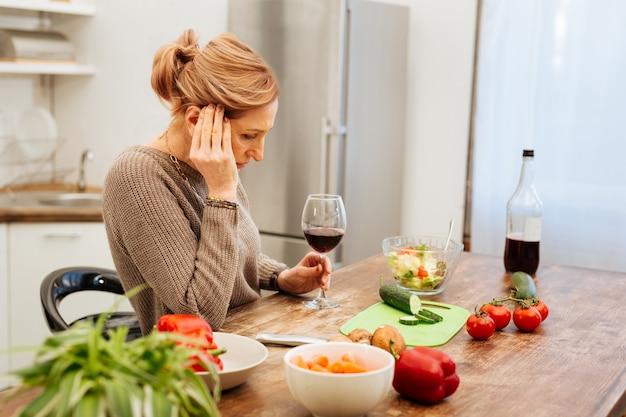 Samo picie wina. smutna dojrzała kobieta jest sama w domu i pije czerwone wino podczas gotowania na kuchennym stole