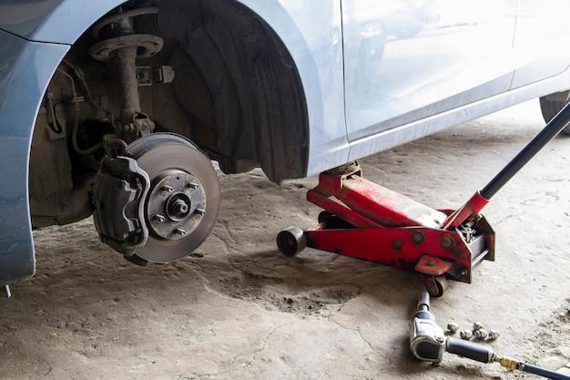 Samochód bez koła i podnoszony hydraulicznie w oczekiwaniu na wymianę opon