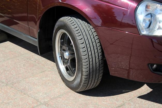 Samochód bordowy. koła samochodów w ostrym słońcu. nowy lśniący samochód i koło w bezpośrednim świetle słonecznym i na świeżym powietrzu stojące na asfalcie.