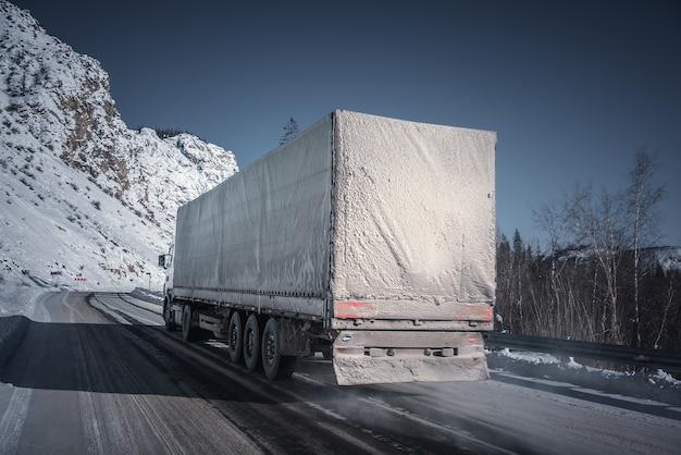 Samochód ciężarowy na zimowej drodze.