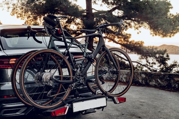 Samochód crossover z dwoma drogowymi rowerami załadowanymi na stojaku zaparkowanym przy nadmorskiej drodze