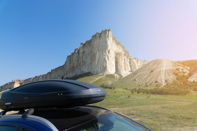 Samochód do podróży z bagażnikiem dachowym po górskiej drodze, na tle białej skały. zdjęcie wysokiej jakości