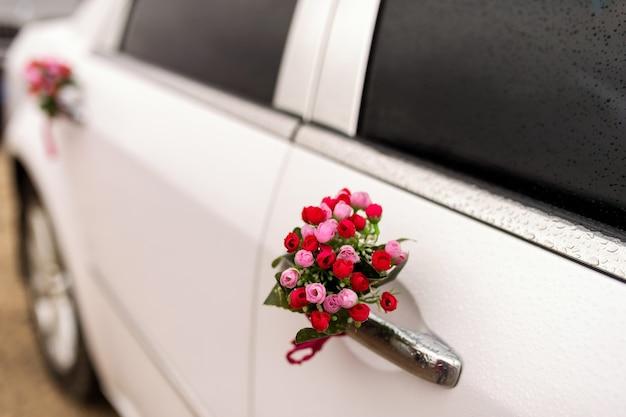Samochód do ślubu z pięknymi dekoracjami kwiatowymi.