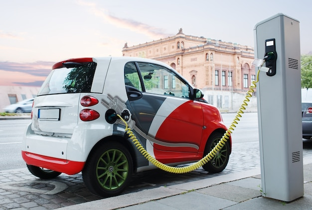Samochód elektryczny ładuje się na ulicy.