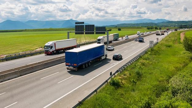 Samochód i ciężarówki pędzące na autostradzie wielopasmowej na obwodnicy turynu, włochy.