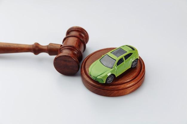 Samochód i drewniany młotek sędziego na białym.