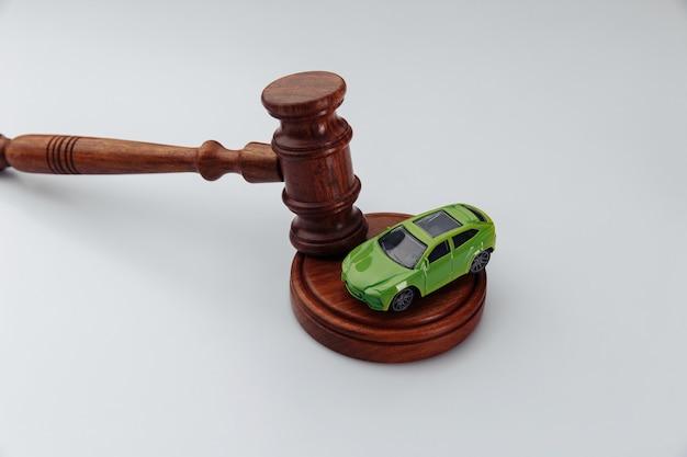 Samochód i sędzia młotek na białej ścianie. koncepcja sprzedaży samochodu w drodze licytacji lub wyroku wypadku.