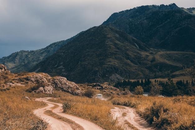Samochód jedzie do przodu po polnej drodze wśród gór i wzgórz