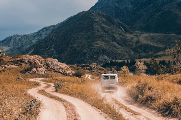 Samochód jedzie do przodu po polnej drodze wśród gór i wzgórz.