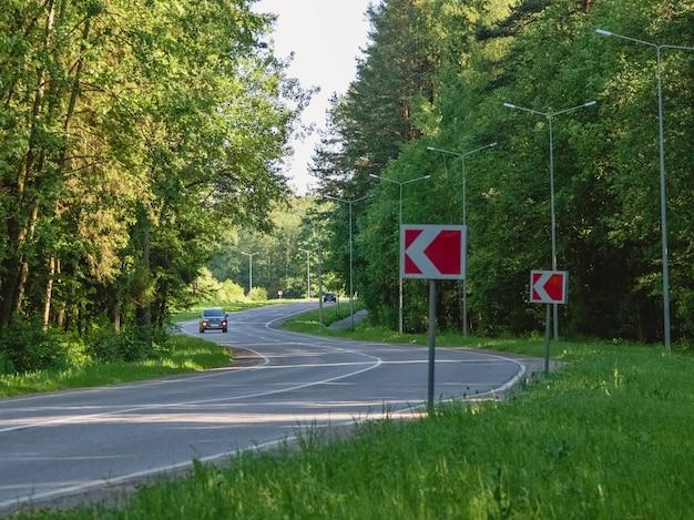 Samochód jedzie na krętej autostradzie w letnim lesie