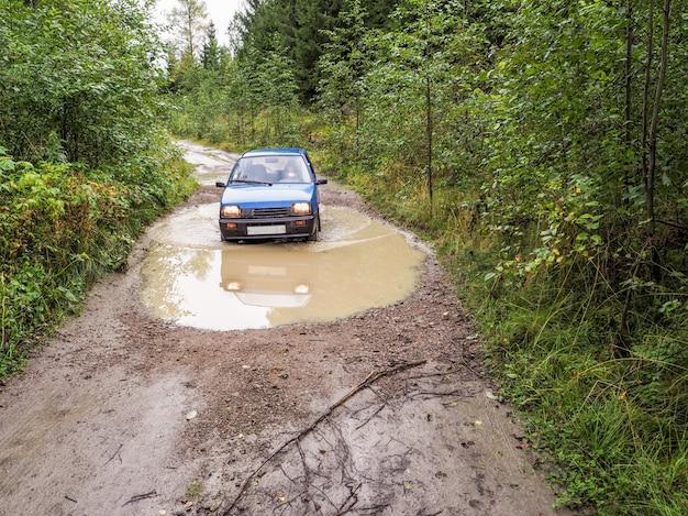 Samochód jedzie przez deszcz zatarcie drogi. samochód w deszczu zatarł drogę.