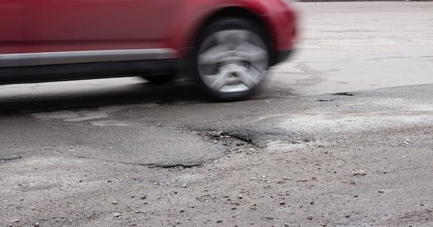 Samochód jedzie wokół dziury na drodze. łamany asfalt po zimie.
