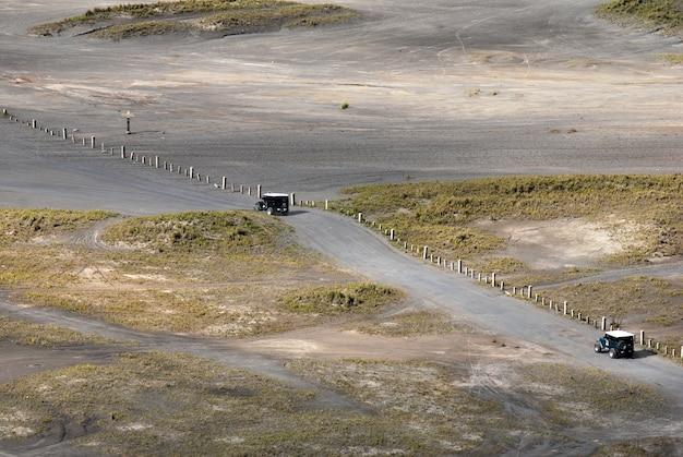 Samochód jeepowy na deserze, który prowadzi przez deser i łąkę przy szemrzącym piasku bromo