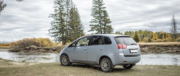 Samochód jest zaparkowany na brzegu rwącej rzeki obok żółtozielonego jesiennego lasu. koncepcja podróży, piękna przyroda i jesienny nastrój