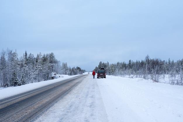 Samochód jest zaparkowany na poboczu zimowej drogi. arktyczny śnieg prosta zimowa droga.
