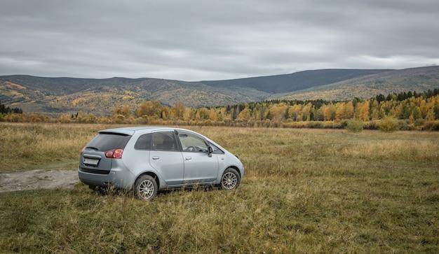 Samochód jest zaparkowany na trawniku przed wzgórzami i żółto-zielonym malowniczym jesiennym lasem. koncepcja podróży, piękna przyroda i jesienny nastrój