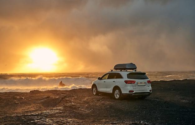 Samochód jest zaparkowany nad brzegiem morza. seascape, wybrzeże z czarnym wulkanicznym piaskiem o zachodzie słońca.
