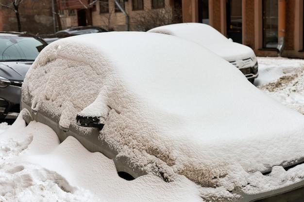 Samochód jest zaśmiecony śniegiem na ulicy miasta zimą