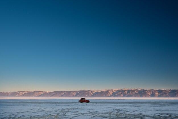 Samochód jeździ zimą po lodzie zamarzniętego jeziora bajkał