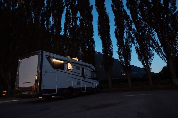 Samochód kempingowy do transportu i wypoczynku osób zaparkowanych nocą w pobliżu lasu leśnego, cieszących się na świeżym powietrzu w podróżniczym stylu życia