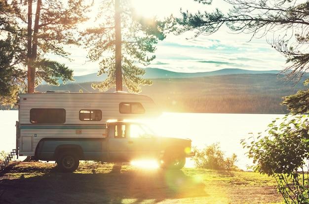 Samochód kempingowy zaparkowany na brzegu jeziora w górach. sezon letni w kanadzie.