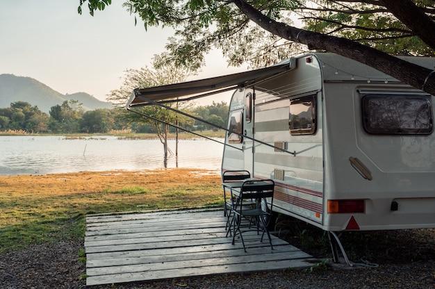 Samochód kempingowy zaparkowany w pobliżu jeziora na kempingu wieczorem na wakacjach