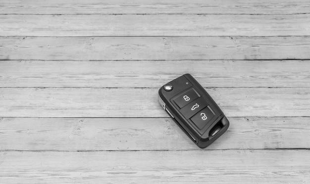 Samochód klucz na stonowanym drewnianym tle, odgórny widok