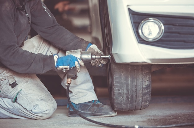 Samochód, mechanik samochodowy zmiana opon, koła w samochodzie kluczem pneumatycznym, serwis