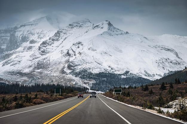 Samochód Na Autostradzie I Zaśnieżonym Paśmie Górskim W Mroku W Icefields Parkway, Kanada Premium Zdjęcia