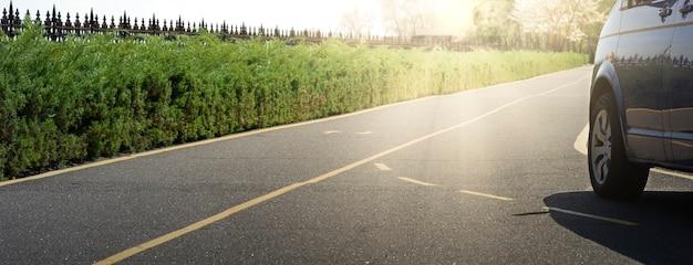 Samochód na drodze asfaltowej w letni dzień w parku. panorama transportu na drodze.