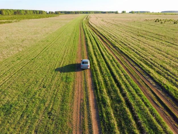 Samochód na drodze na zielonym polu zdjęcie z drona