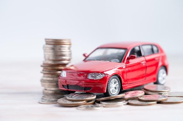 Samochód na stosie monet. koncepcje kredytu samochodowego, finansów, oszczędzania, ubezpieczenia i leasingu.