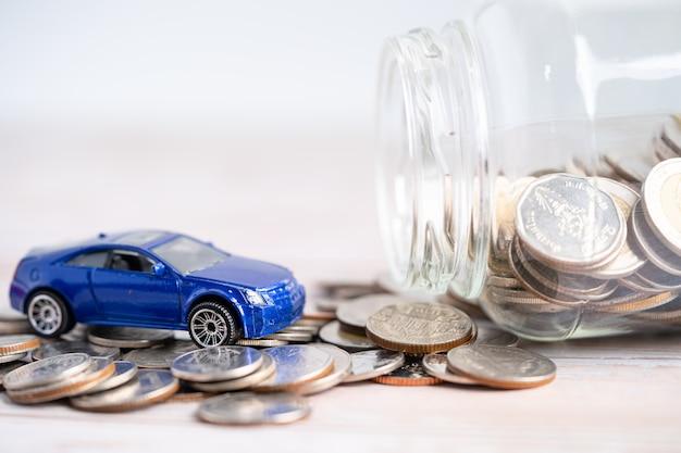 Samochód na tle monet kredyt samochodowy finanse oszczędność pieniędzy ubezpieczenie i leasing