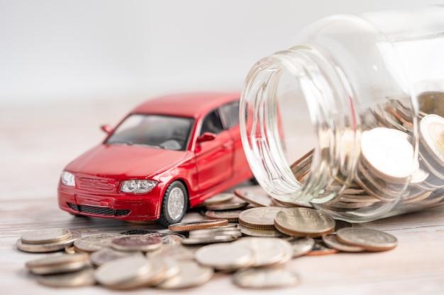 Samochód na tle monet pożyczka samochodowa finanse oszczędzanie pieniędzy