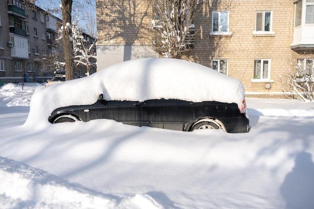 Samochód na ulicy pokrytej dużą ilością śniegu po potężnej burzy śnieżnej