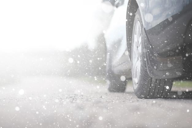 Samochód na wiejskiej drodze w pierwszy jesienny śnieg. pierwszy zimowy śnieg na wiejskiej drodze, samochód pod śniegiem.