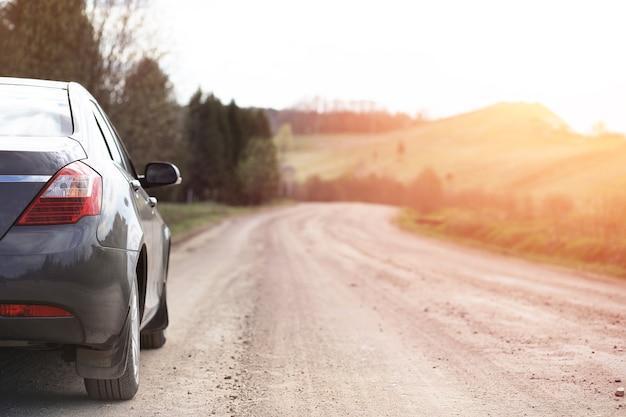 Samochód na wiejskiej i zakurzonej drodze na tle zachodu słońca