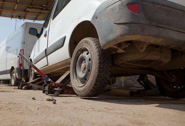 Samochód naprawiony w garażu, podnośnik hydrauliczny podnieść samochód, koło bez opony