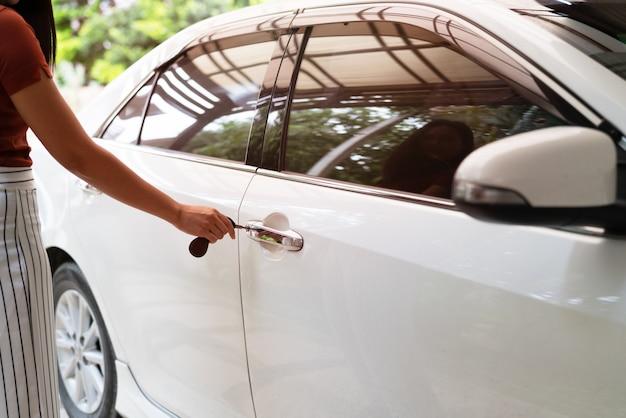 Samochód odblokowuje się, kobieta używa klucza do otwierania drzwi samochodu