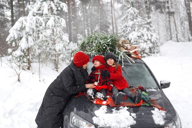 Samochód oraz mama i córki w środku lasu z choinką i prezentami
