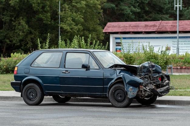 Samochód po wypadku zaparkowany, maska zerwana, konsekwencje nieuwagi na drogach.