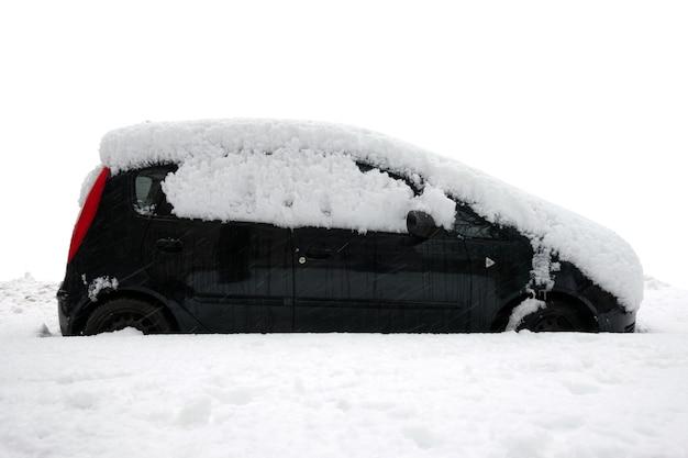 Samochód pod grubą warstwą śniegu po burzy na białym tle.