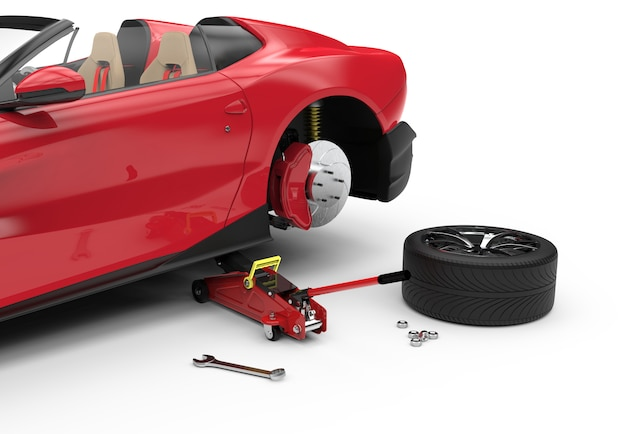 Samochód podniesiony z czerwonym hydraulicznym podnośnikiem podłogowym do naprawy