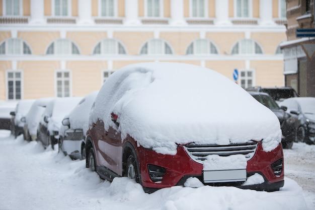 Samochód pokryty grubą warstwą śniegu. ulica sankt petersburga po największej burzy śnieżnej