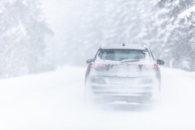 Samochód pokryty śniegiem jazdy w śnieżycy w mroźny zimowy dzień w lesie.